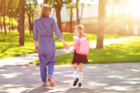 Parent and pupil of primary school go hand in hand. Woman and girl with pink backpack behind the back. Beginning of lessons. First day of fall Imagens