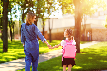 Parent and pupil of primary school go hand in hand. Woman and girl with pink backpack behind the back. Beginning of lessons. First day of fall Standard-Bild - 124528684