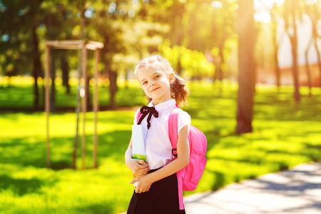Smiling student girl wearing school backpack and holding exercise book. Portrait of happy Caucasian young girl outside the primary school. Smiling schoolgirl looking at camera.