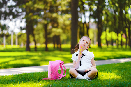 Little school girl with pink backpack sitting on grass after lessons and thinking ideas, read book and study lessons, writing notes, education and learning concept.