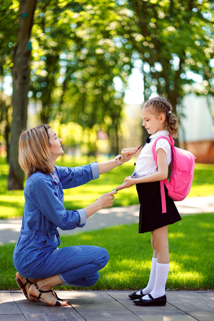 First day at school. mother leads a little child school girl in first grade. Woman and girl with backpack behind the back. Beginning of lessons. First day of fall