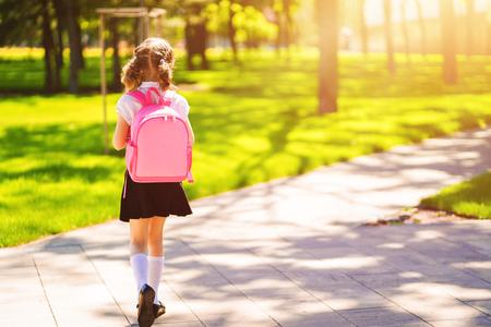 Piękna mała dziewczynka z plecakiem spaceru w parku gotowy powrót do szkoły, widok z tyłu, upadek na zewnątrz, koncepcja edukacji. Zdjęcie Seryjne