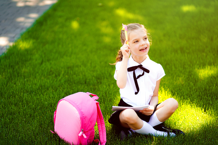 Bingo. Niña de la escuela con mochila rosa sentada en la hierba después de lecciones y pensar ideas, leer libros y estudiar lecciones, escribir notas, concepto de educación y aprendizaje.