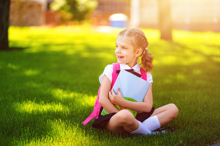 Little school girl with pink backpack sitting on grass after lessons looking side away, read book or study lessons, thinking ideas, education and learning concept. Foto de archivo