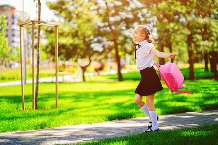 Porträt des tragenden Schulrucksacks des glücklichen kaukasischen jungen lächelnden Mädchens außerhalb der Grundschule. Schulmädchen, Grundschülerin läuft von der Schule springen, Abschluss, Sommerferien.