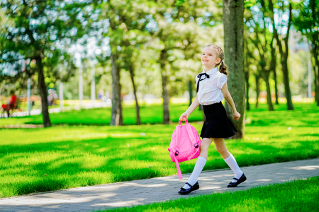 Portrait of happy Caucasian young smiling girl wearing school backpack outside the primary school. schoolgirl, elementary school student runs jumping from school, graduation, summer holidays. 版權商用圖片