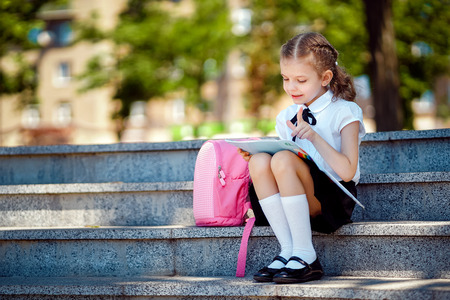Pupil of primary school read book sitting on stairs. Girl with backpack near building outdoors. Beginning of lessons. First day of fall.