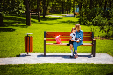 Mother and little daughter in outdoors public park sitting on the bench and read book, study lessons. Parenthood and child concept. Mother kissing her child.