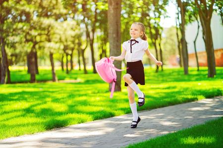 Retrato de feliz sonriente joven caucásica vistiendo mochila escolar fuera de la escuela primaria. colegiala, estudiante de escuela primaria corre saltando de la escuela, graduación, vacaciones de verano. Foto de archivo