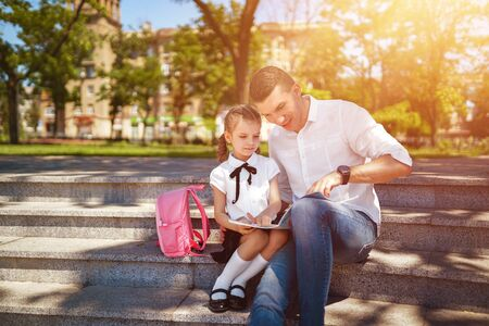 first day at school. Father and little kid daughter sitting on stairs and read book, study lessons. Parenthood and child concept.