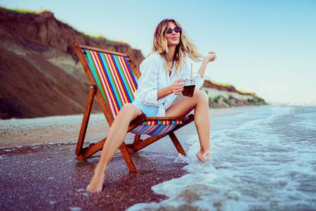 Pretty blonde woman in the shape of a heart sunglasses, white shirt and stripped swimsuit relaxing on a lounger beach and drinks coctail. summer vacation concept.