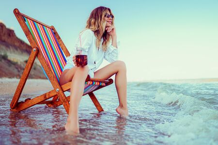 Pretty blonde woman in the shape of a heart sunglasses, white shirt and stripped swimsuit relaxing on a lounger beach and drinks coctail. summer vacation concept. Banco de Imagens