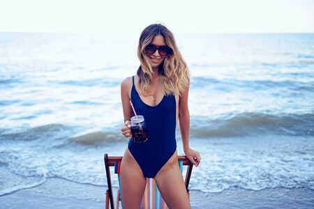 Awesome beauty blonde woman in sunglasses, swimsuit relaxing on beach and drinks coctail. summer vacation concept.