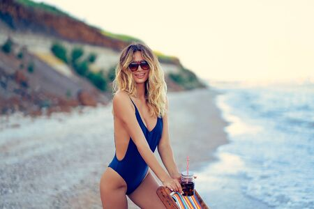 Awesome beauty blonde woman in sunglasses, swimsuit relaxing on beach and drinks cocktail. summer vacation concept. 版權商用圖片