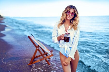 Pretty blonde woman in the shape of a heart sunglasses, white shirt and stripped swimsuit relaxing on beach and drinks cocktail. summer vacation concept.