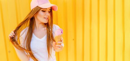 Outdoor fashion portrait of young hipster girl with ice-cream on yellow wall background.