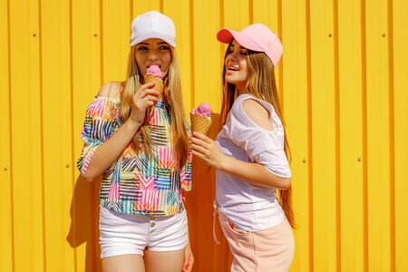 Lifestyle portrait of two beautiful best friend hipster lady wearing stylish bright outfits and having great time. Standing near yellow wall enjoying day off and eating sweet cold ice-cream. 版權商用圖片