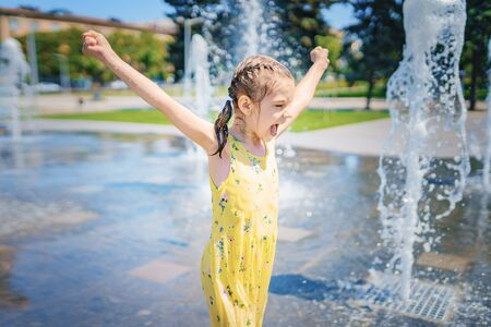 Girl in yellow dress playing and having fun enjoying the spray of the fountain. Summer fun concept.