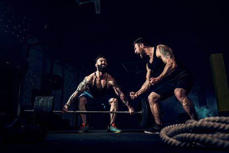 Two muscular bearded tattoed athletes training, one lift heavy weight bar when other is motivating. Scream. Working hard. Exercise for the muscles of the back Banque d'images
