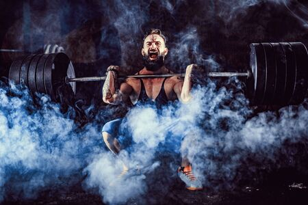 Muscular bearded tattoed fitness man doing deadlift a barbell over his head in modern fitness center. Functional training. Snatch exercise