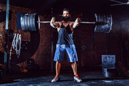 Muscular bearded tattoed fitness man doing deadlift a barbell over his head in modern fitness center. Functional training. Snatch exercise Stock Photo
