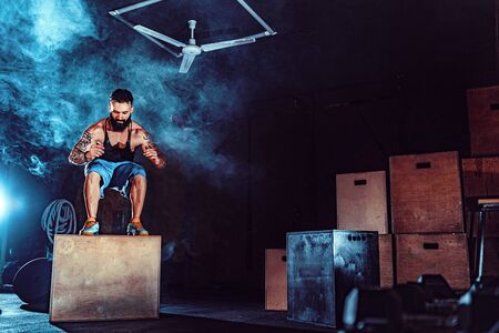 Fit tattoed bearded man jumping onto a box as part of exercise routine. Man doing box jump in the gym. Athlete is performing box jumps. Archivio Fotografico