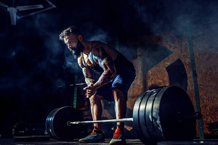 Muscular fitness man preparing to deadlift a barbell over his head in modern fitness center. Functional training. Snatch exercise