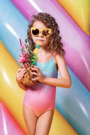 Pretty smiling girl wearing pink and blue swimwear and sunglasses holding pineapple cocktail with colorful straws and showing thumb up on rainbow inflatable mattress background