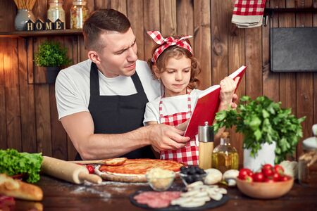 Girl wearing checkered apron reading red recipes book while father spreading sauce by dough for pizza in stylish wooden kitchen