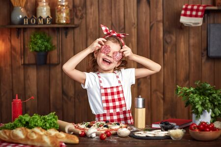 Adorable little female chef wearing checkered apron and headband cooking pizza and making face with salami slices instead eyes and opened mouth on stylish wooden kitchen Banco de Imagens