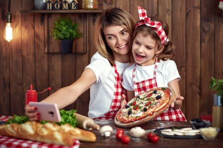 Beautiful mother and daughter wearing white T-shirts, checkered aprons and headbands smiling and taking selfie with cooked pizza on pink cellphone in stylish kitchen interior. Stok Fotoğraf