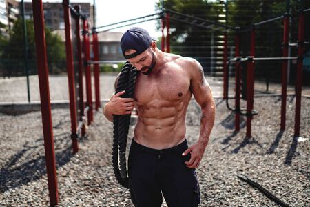 Athletic looking man holding battle rope at street gym yard. Strength and motivation. Outdoor workout. Stock Photo