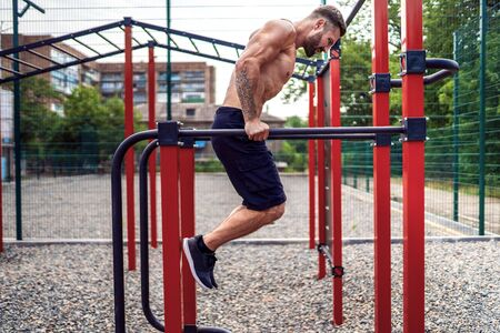 Strong muscular man doing push-ups on uneven bars in outdoor street gym. Workout lifestyle concept. 스톡 콘텐츠