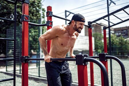 Strong muscular man doing push-ups on uneven bars in outdoor street gym. Workout lifestyle concept. Stock Photo