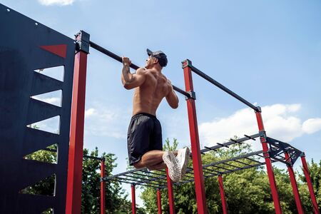 Brutal athletic man making pull-up exercises on a crossbar at outdoor streeet gym.