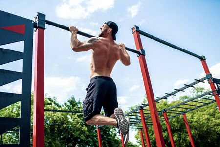 Brutal athletic man making pull-up exercises on a crossbar at outdoor street gym.