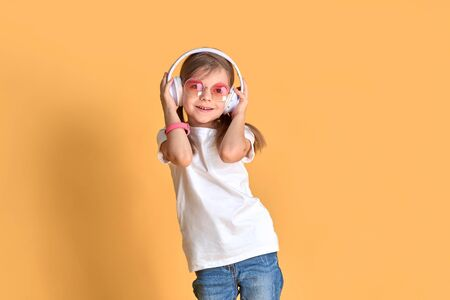 Girl listening music in headphones on yellow background. Cute child in colored sunglasses enjoying happy dance music, smile, posing on pink studio background wall.