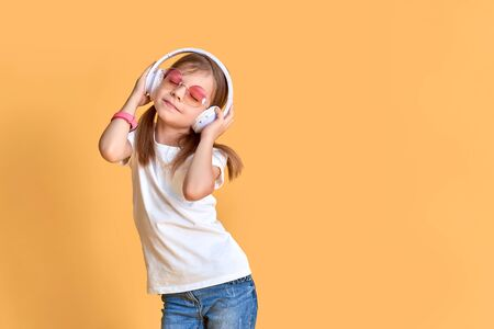Girl listening to music in headphones on yellow background. Cute child in colored sunglasses enjoying happy dance music, smile, posing on pink studio background wall. Stock Photo
