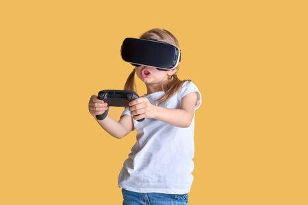 Girl experiencing VR headset vs joystick game on yellow background. Surprised emotions on her face. Child using a gaming gadget for virtual reality. Futuristic goggles at young age. Virtual technology 스톡 콘텐츠