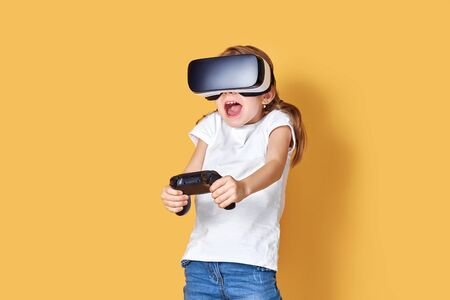 Girl experiencing VR headset vs joystick game on yellow background. Surprised emotions on her face. Child using a gaming gadget for virtual reality. Futuristic goggles at young age. Virtual technology Stock Photo