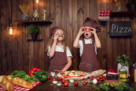 Adorable little girls chef wearing aprons and headbands cooking pizza and making face with tomatoes instead eyes and lettuce, opened mouth on stylish wooden kitchen