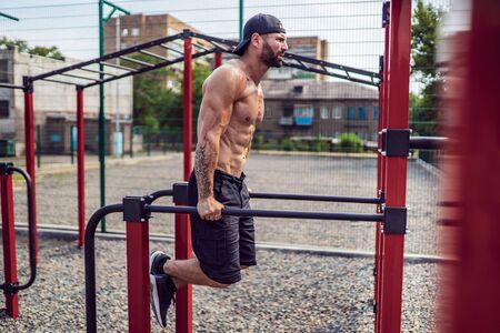 Strong muscular man doing push-ups on uneven bars in outdoor street gym. Workout lifestyle concept. Фото со стока