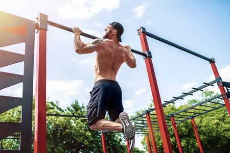 Brutal athletic man making pull-up exercises on a crossbar at outdoor street gym. Back view.