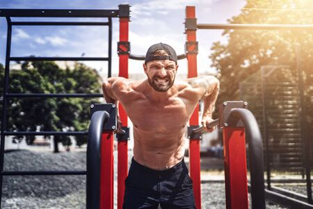 Strong muscular man doing push-ups on uneven bars in outdoor street gym. Workout lifestyle concept. Stock fotó