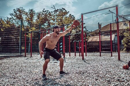 Athletic man working out with a kettlebell at street gym yard. Strength and motivation. Outdoor workout. Exercise for shoulders.