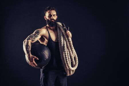 Bearded athletic looking bodybuilder holding battle rope on dark studio background with smoke. Strength and motivation.