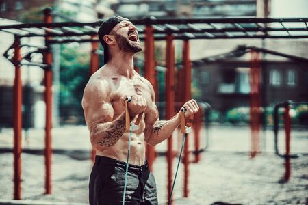 Fitness man exercising with stretching band. Muscular sports man exercising with elastic rubber band. Guy working out with rubber band. Fit, fitness, exercise, workout and healthy lifestyle