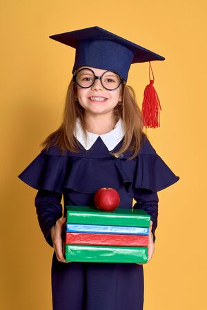 School Girl in academician clothes with book and apple on yellow stduio background Stock fotó