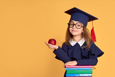 Charming smart girl in glasses and graduation clothes holding red apple while standing at pile of colourful books over yellow background Stock fotó