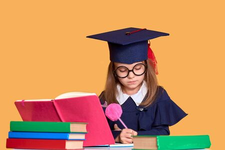 Diligent girl in glasses and graduation clothes studying with textbooks while sitting at desk with colourful books and pen over yellow background